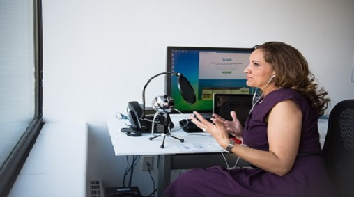 Women using microphone in front of laptop at desk