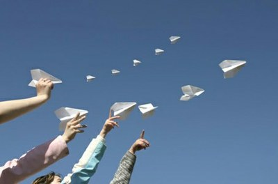 Hands throw multiple paper planes up into a blue sky
