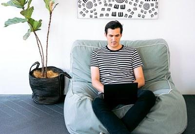 Man sitting on cushion with laptop