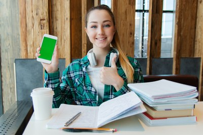 Smiling women holding phone with books and folder